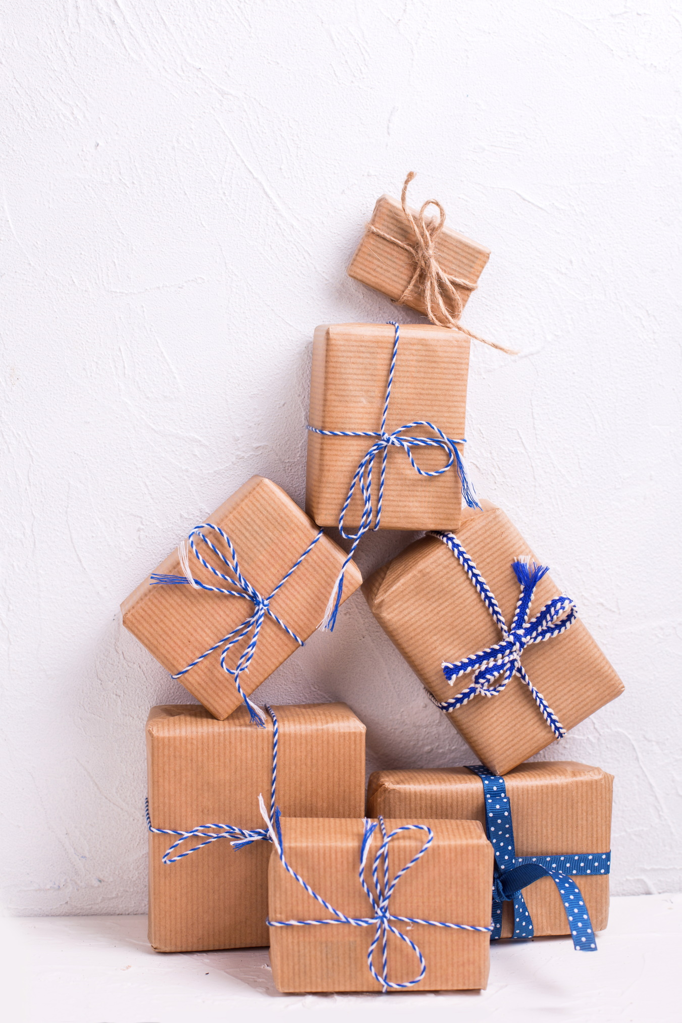 Stack of wrapped boxes with presents  on white textured background. Selective focus.  Winter holiday, Christmas, New Year. Vertical image.